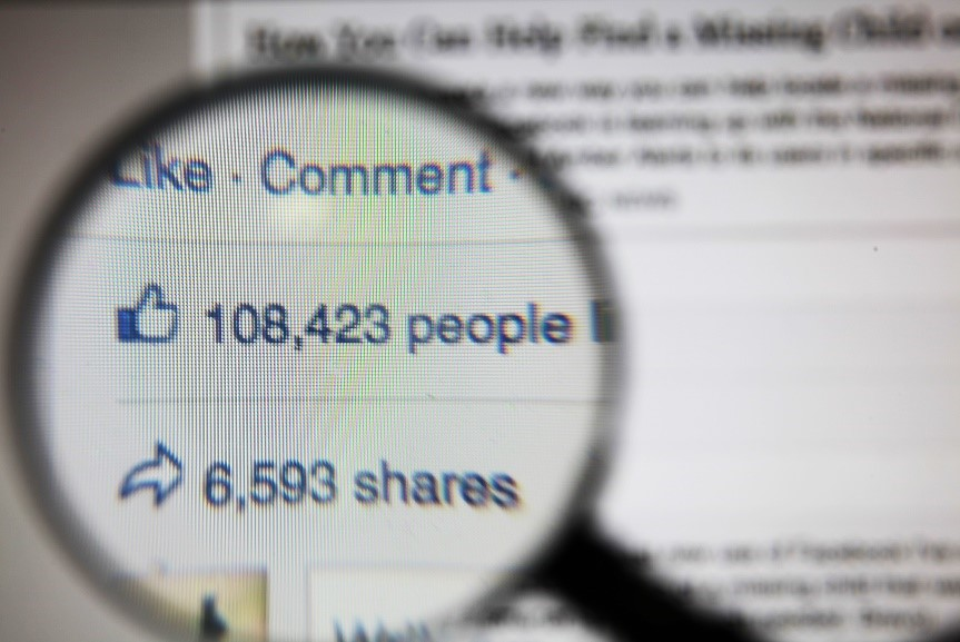 magnifying glass over Facebook data of likes and shares