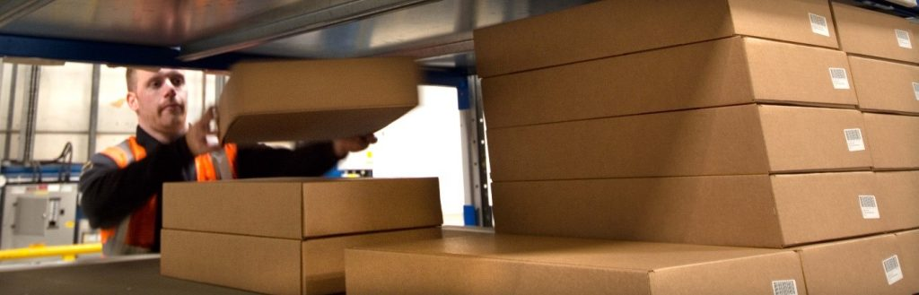 ICT Reverse employee stacking boxes onto a warehouse shelf
