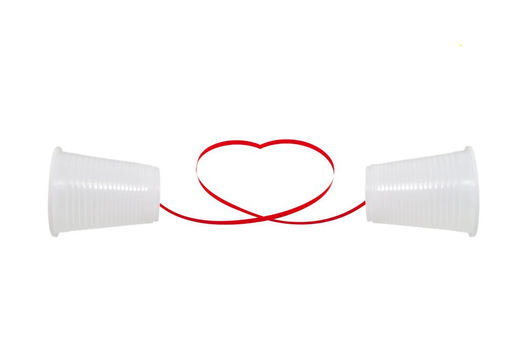 Long distance relationship concept. 2 white plastic cups connected with a red thread